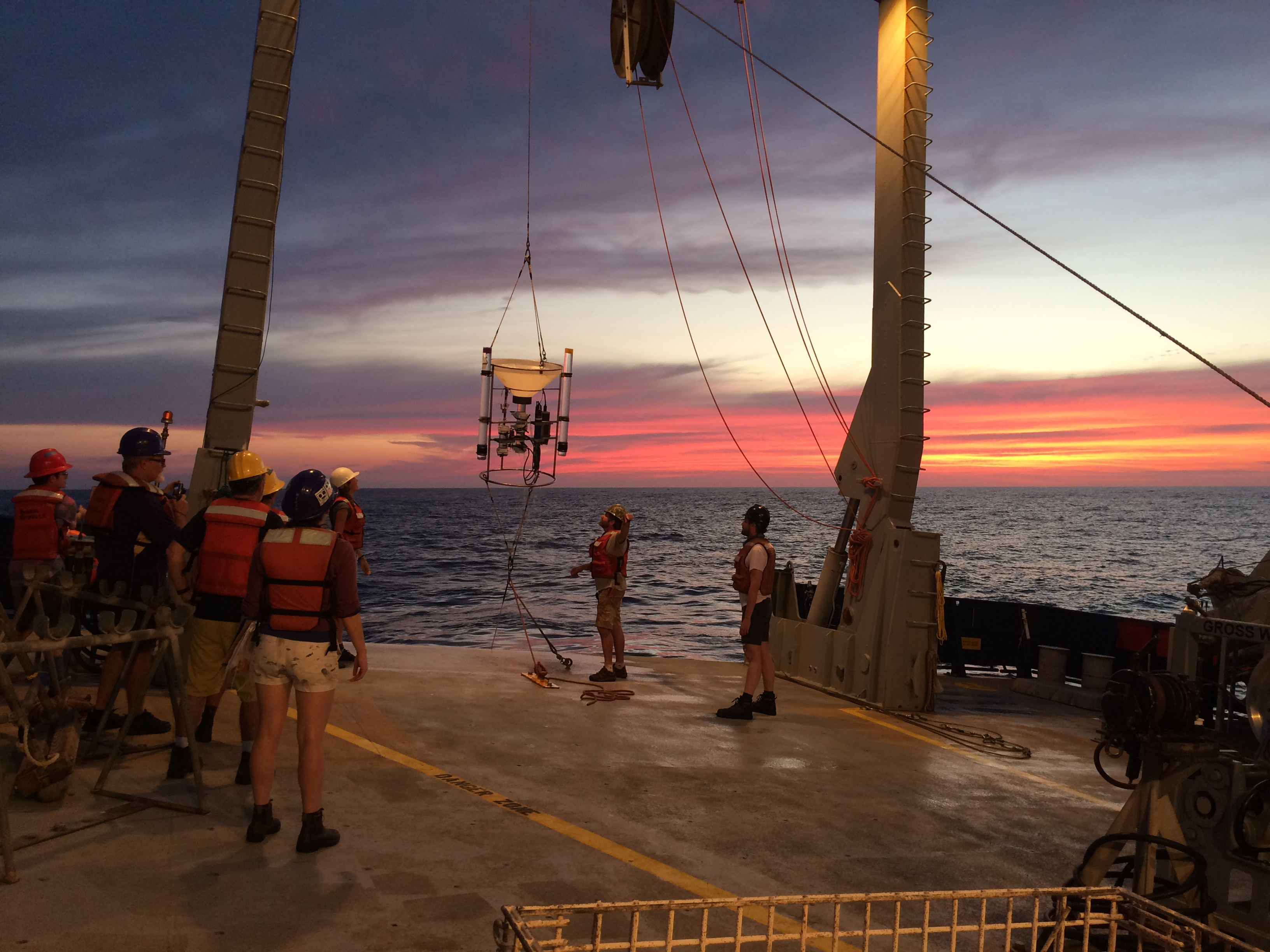 Scientists watch from a ship deck as a sample is hauled in from the ocean.