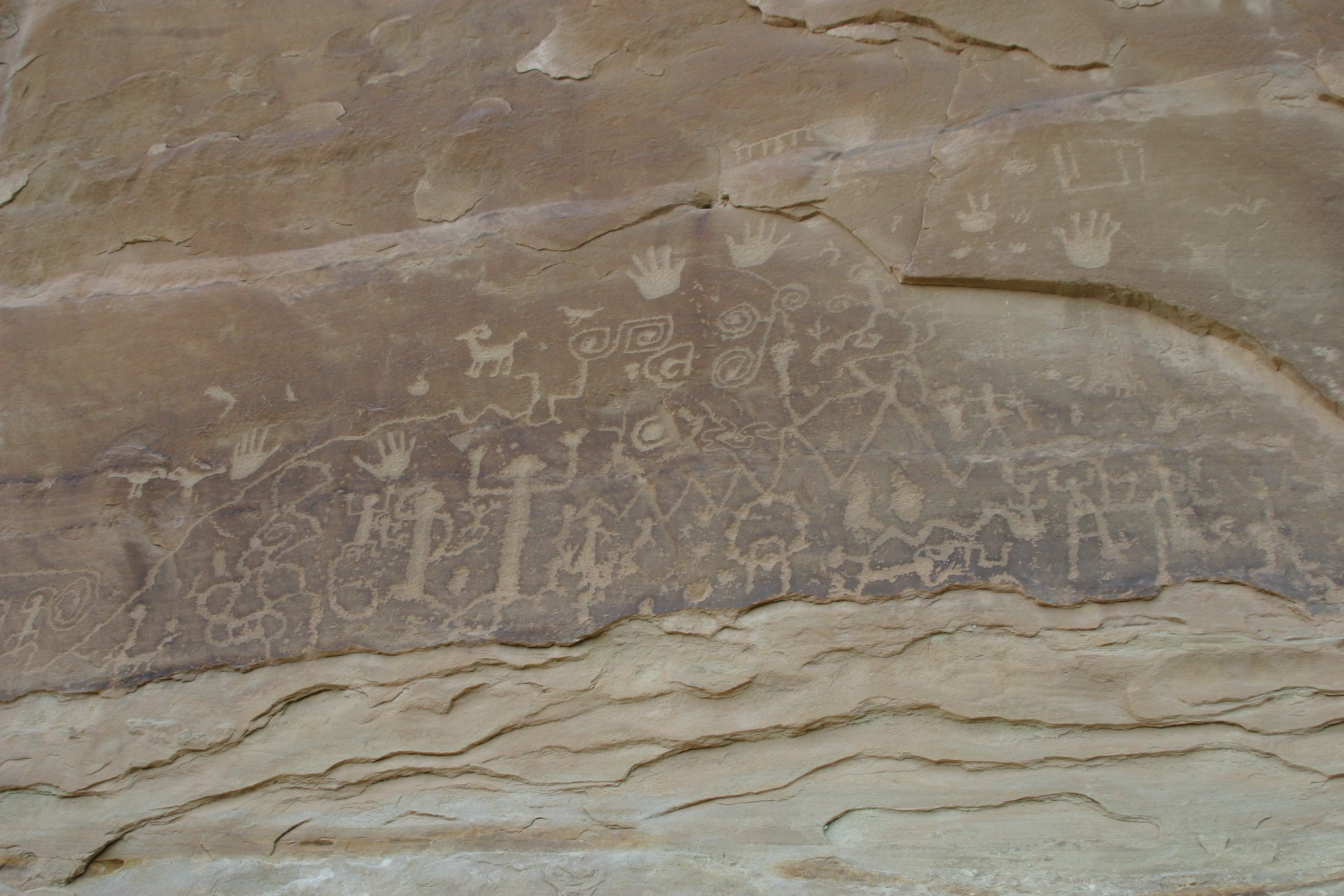 Rock art featuring human and animal forms and handprints