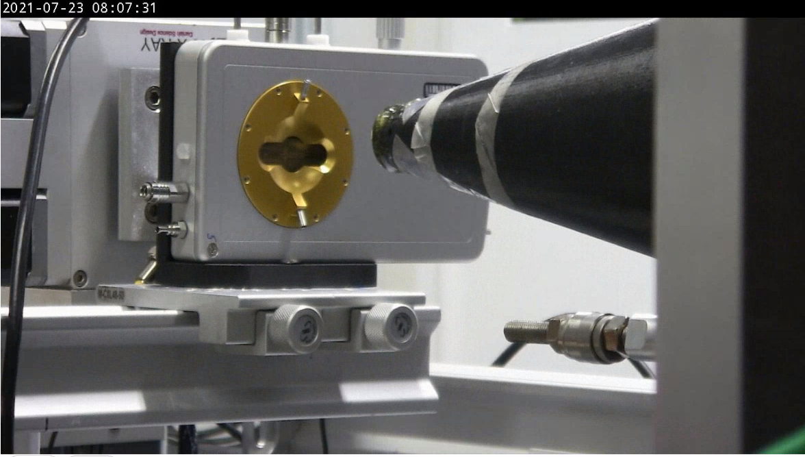 An X-ray beam line guide points toward a gold-colored piece of laboratory equipment.