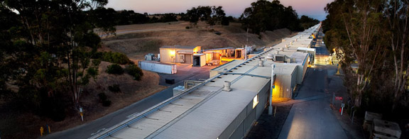 PHOTO: SLAC's linear accelerator above ground housing at night.