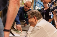 Image - Phil Manning, from left, Pete Larson, Victoria Egerton, and Arjen van Veelen view a fossil sample during a visit to SLAC's Stanford Synchrotron Radiation Lightsource last year. (Matt Beardsley/SLAC)