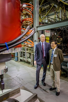 CPI President and Chief Operating Officer Robert A. Fickett, left, and SLAC Lab Director Chi-Chang Kao look at one of the XL5 klystrons the company built under a cooperative agreement with SLAC.