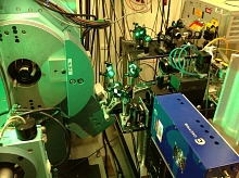 "Photo - Green laser light is visible in an experimental setup at SLAC's SSRL. Infared laser light was ""frequency-doubled"" to produce this green laser light. The large apparatus on the left is an X-ray diffractometer that was used to align the sample."