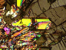 Image - This image shows an illuminated stishovite crystal (yellow). Stishovite is a hard, compressed form of silica that ordinarily appears clear or translucent. Researchers confirmed the rapid transformation of silica to stishovite in a SLAC experiment.