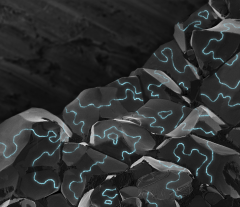 An illustration of electrically conductive areas (blue) along the boundaries of tiny magnetic regions, or domains, in chunky grains of a material that normally doesn't conduct electricity.